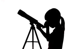 Silhouette of little girl looking through a telescope Stock Photo