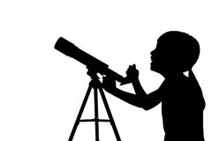 Silhouette of little girl looking through a telescope Royalty Free Stock Image