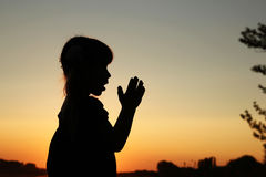 Silhouette of a little girl praying Royalty Free Stock Image