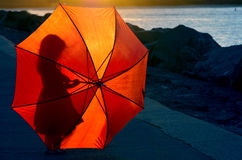 Silhouette of little girl with umbrella. Silhouette of a little girl (age 04) with red umbrella during sunset Stock Images