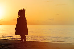 Silhouette of little girl walking at sunset Stock Images