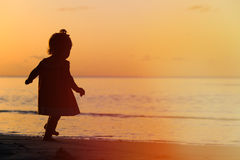 Silhouette of little girl walking at sunset Royalty Free Stock Images