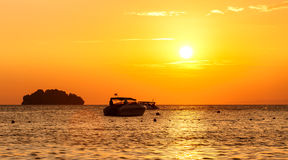 Silhouette of a little island and small boat at sunset Stock Images