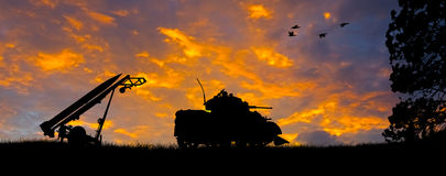 Anti-Aircraft Missile and Tank Silhouette. Silhouette of a Little John Missile and a tank against an evening sunset Stock Image