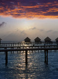 Silhouette of lodges in the sea at sunset. Maldives Stock Photos