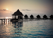 Silhouette of lodges in the sea at sunset. Maldives Stock Images
