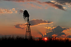 Silhouette of a lone windmill at sunset. A solitary windmill on a South African farm at sunset stock images