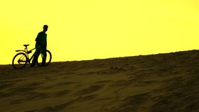 Silhouette of lonely biker walking with his bike along sand dune, yellow sunset colors Stock Photos