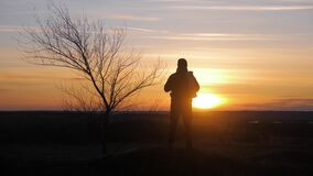 Silhouette lonely man with backpack in the mountains walking at the setting sun and the sunset. The concept of tourism