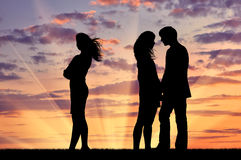 Silhouette of a lonely woman near loving couple Stock Photo