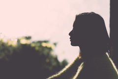 Silhouette of lonely woman. Silhouette portrait of lonely young woman sitting during dusk time Stock Photography