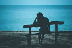 Silhouette of lonely woman sitting on wooden bench on the beach and looking to blue sea. Silhouette of lonely woman sitting on wooden bench on the beach and Royalty Free Stock Photography