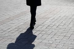 Silhouette of lonely woman walking down the street, black shadow on pavement. Slim female legs outdoor, concept of loneliness, diet, dramatic life story royalty free stock photography