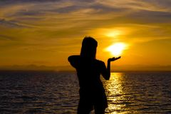 The silhouette of Long-haired woman standing Hands up to get the sunset royalty free stock photo