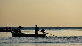 Silhouette Long-tail boats sailing on the andaman sea with golden light of the Sun  before sunset. Travel video silhouette Long-tail boats sailing on the andaman stock footage