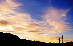 Silhouette of a lost hiker. Hiker looking on a sign to find the right path royalty free stock image