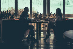 The silhouette of the love couple sitting in cafe Royalty Free Stock Photography