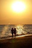 Silhouette of love couple walking on beach. Silhouette of romantic love couple walking on beach hand in hand at sunset Royalty Free Stock Photo