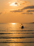 Silhouette of a lovely couple on a canoe boat during sunset. Silhouette of two people on a kayak at sea beach at twilight time Stock Photo