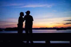Silhouette of lovely couple on lake stock images