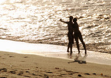 Silhouette of lovers on the beach Stock Photography