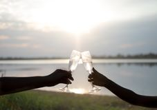 Silhouette. Lovers hand with glasses of champagne against the sunset and sky background royalty free stock images