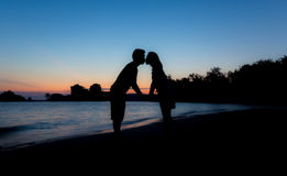 Silhouette of Lovers Kissing on the Beach at Twilight Royalty Free Stock Photography