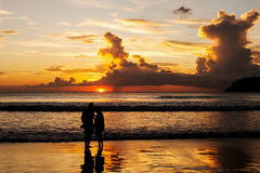 Silhouette of lovers relax on the beach Royalty Free Stock Images