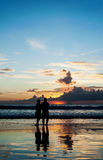 Silhouette of lovers relax on the beach Stock Images