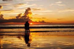 Silhouette of lovers relax on the beach Royalty Free Stock Photography