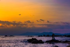 Silhouette of lovers on stones on the seashore, at sunset, in th stock image