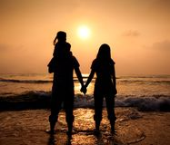 The silhouette of loving asian family. Walking while holding hands on beach at sunset Royalty Free Stock Image