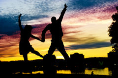 Silhouette of loving Couple. A loving couple jump in the air creating a heart shape silhouette at sunset stock photos