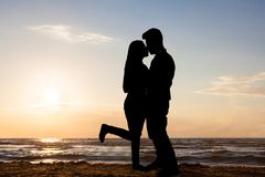 Silhouette of loving couple at beach Stock Photos