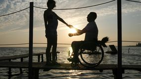 Silhouette of loving couple with disabled person on seafront near shiny water in bright beams. Silhouette of loving couple with disabled person met on seafront stock video