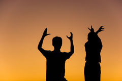 Silhouette of loving couple with hands in L,O,V,E shape Stock Images