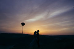 Silhouette of a loving couple kissing in the sunset Stock Photography