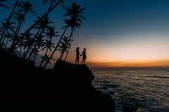 Silhouette of loving couple on sea. Man and woman at sunset. Honeymoon on the Islands. Man and woman meet sunset. Happy loving stock photos