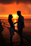 Silhouette of a loving couple at sunset. A silhouette of a loving couple at sunset Royalty Free Stock Image