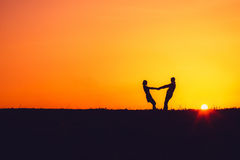 Silhouette of a loving couple at sunset. Silhouette of a loving couple at orange sunset Stock Image