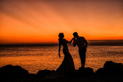 Silhouette of a loving, married couple where he is kissing her h Royalty Free Stock Photo