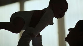 Silhouette Loving mother playing with her baby in home. Shot in Full HD - 1920x1080, 30fps stock footage