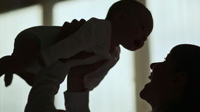 Silhouette Loving mother playing with her baby. Shot in Full HD - 1920x1080, 30fps stock footage