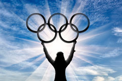 Silhouette ?lympic athlete raised his hands and holds olympic rings. Olympic athlete raised his hands and holds Olympic rings on background of sun. Sport concept Royalty Free Stock Images
