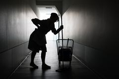 Silhouette of maid suffering from backache. Silhouette Of Female Maid With Mop Suffering From Backache In Corridor Stock Photography