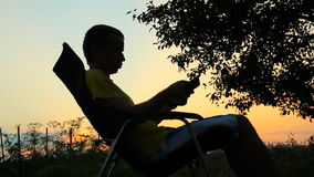 Silhouette of male in chair playing in tablet. Against the background of an orange sky after sunset stock video footage