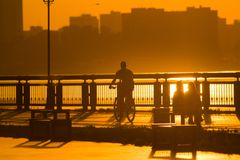 Silhouette of male cyclist on the promenade at sunset. Horizontal Royalty Free Stock Image