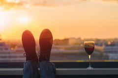 Silhouette of male feet in the shoes with glass of red wine on the sunset town background. Silhouette of male feet in the shoes with glass of red wine on the Stock Photo