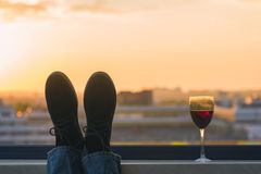 Silhouette of male feet in the shoes with glass of red wine on the sunset town background. Silhouette of male feet in the shoes with glass of red wine on the Stock Photos