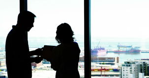 Silhouette of male and female executives discussing over digital tablet. In office